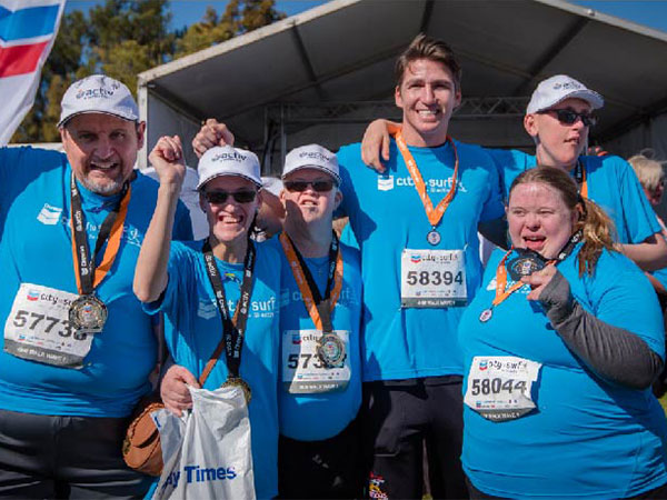 Activ customers and staff cheer and hold up medals after completing the City to Surf.