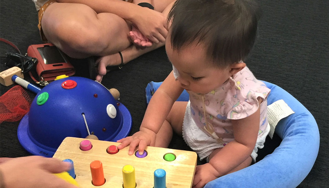 ALDC customer Erin plays with wooden toys.
