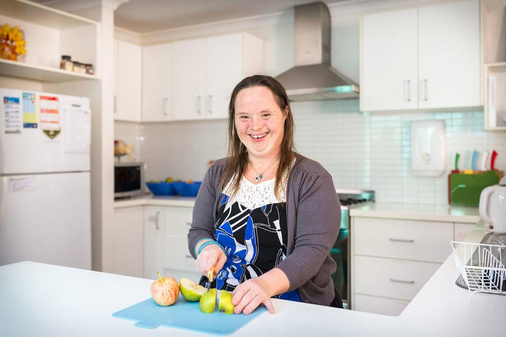 Activ customer Aeron cuts apples in the kitchen.