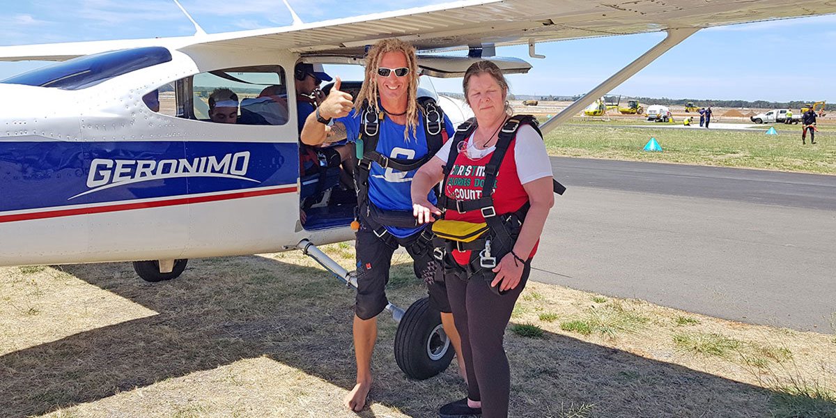 Activ customer Maree stands with skydiving instructor in front of the airplane.