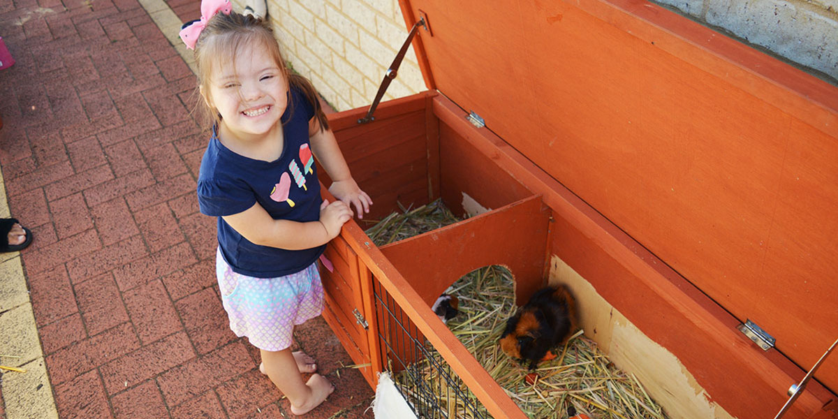 Activ customer Mia smiles at the camera while feeding the guinea pigs.
