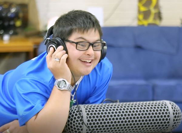 Activ customer Julius smiles while listening to music through headphones.