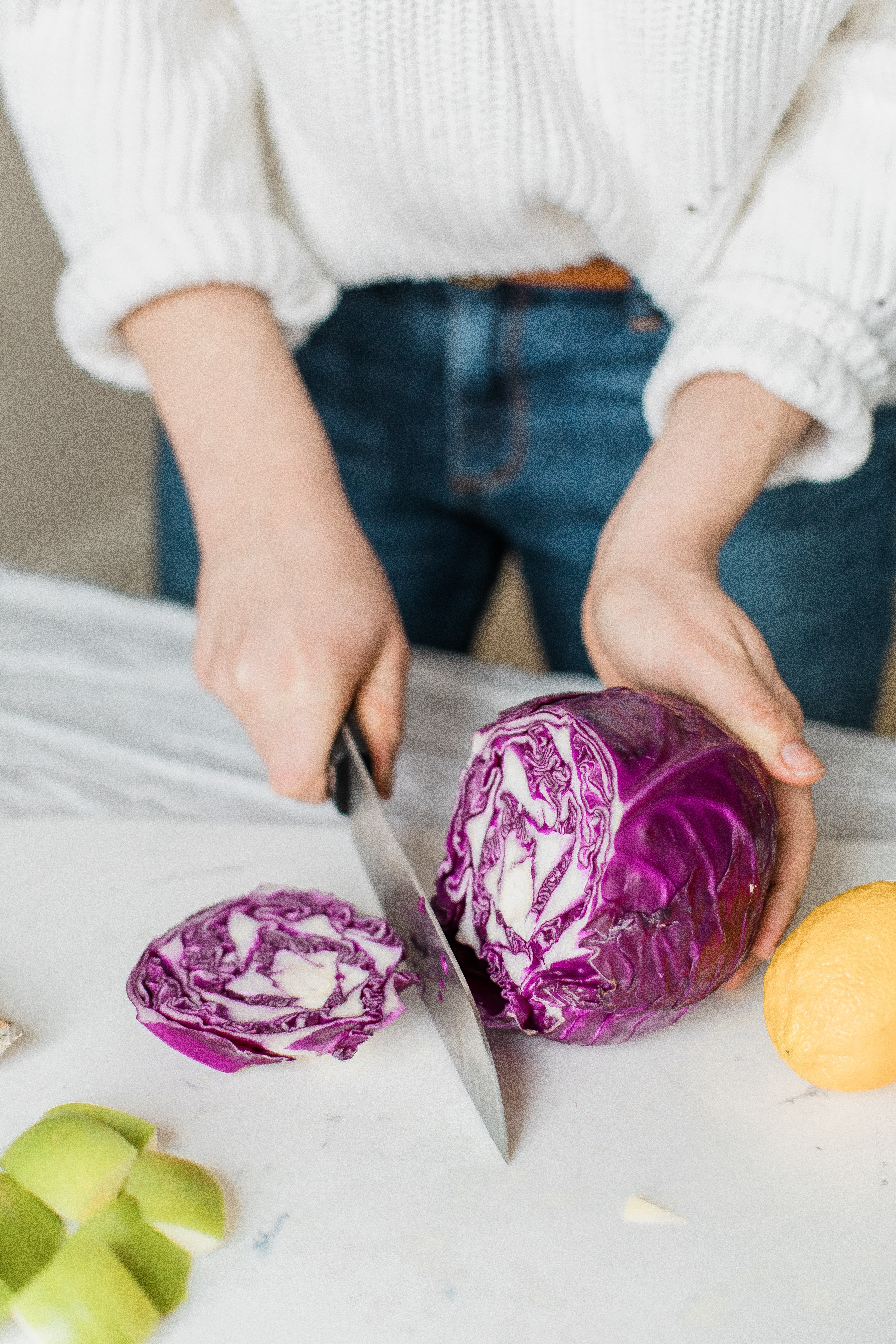 Woman cuts red cabbage in the kitchen