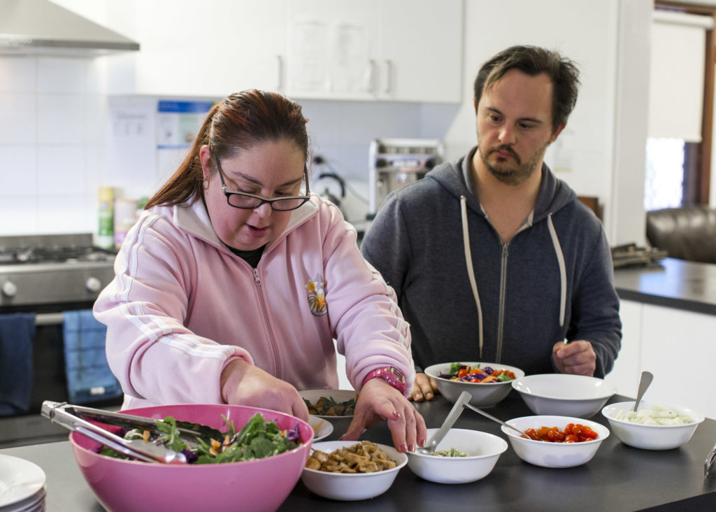 Individuals preparing a meal in supported accommodation
