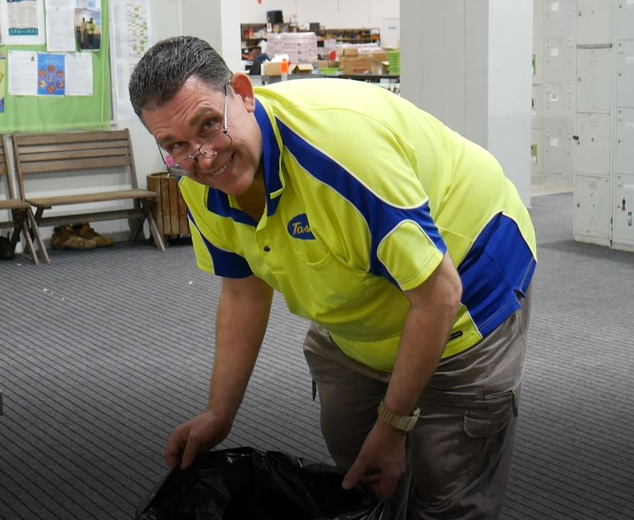Matthew smiles at the camera while emptying the bin